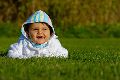 Portrait of baby girl on green grass