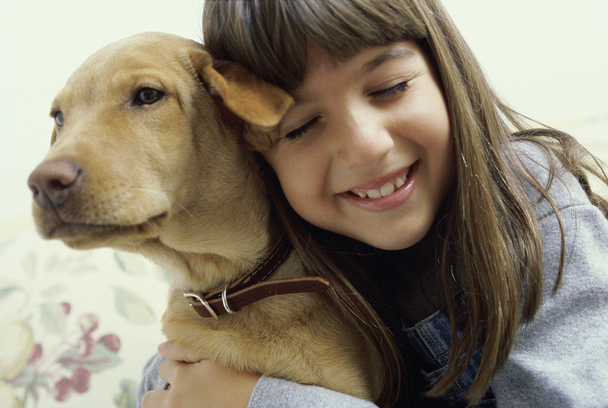 Close-up of girl (8-9) holding her dog