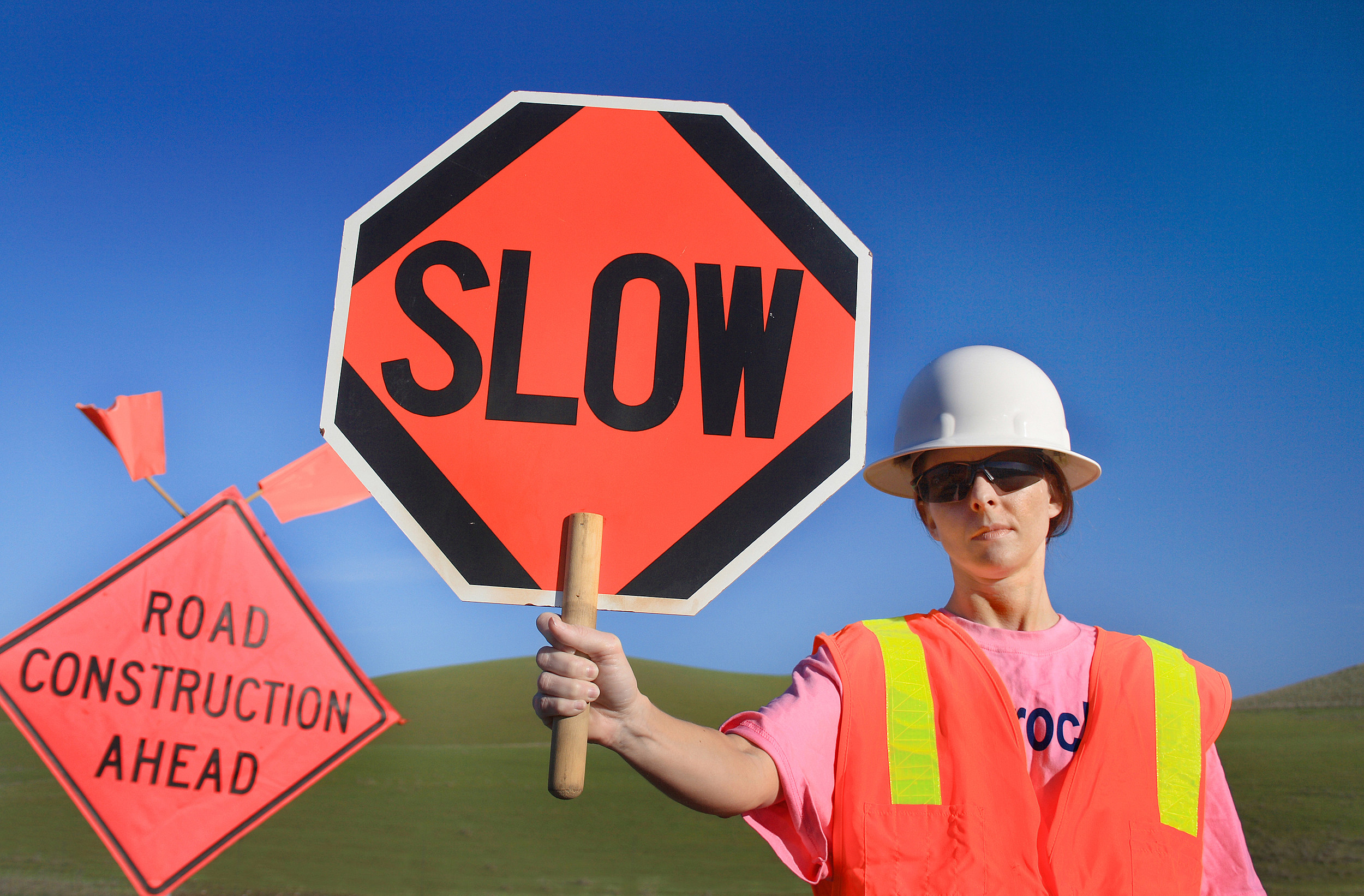 Woman Construction Worker with Slow Sign