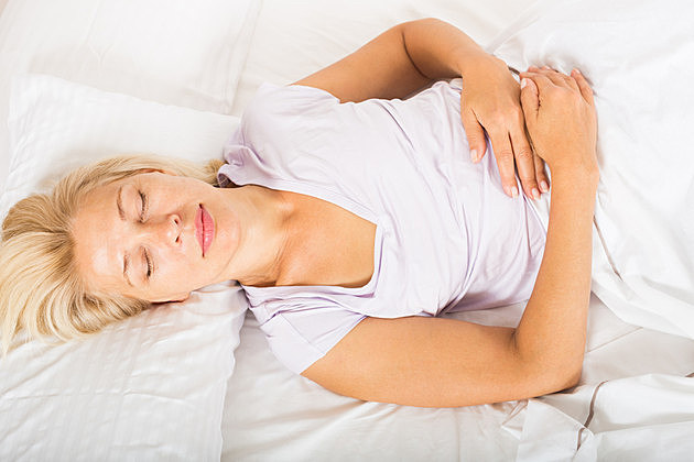 Blonde middle-aged female sleeping on white pillow in bed at home